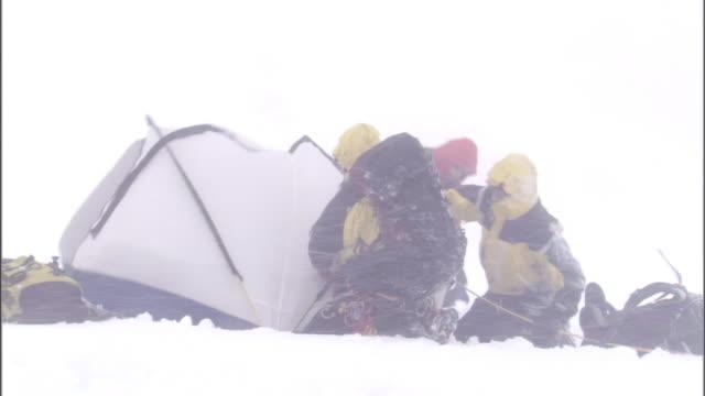 vídeos y material grabado en eventos de stock de hikers in winter gear set up a tent in a blizzard storm. - supervivencia