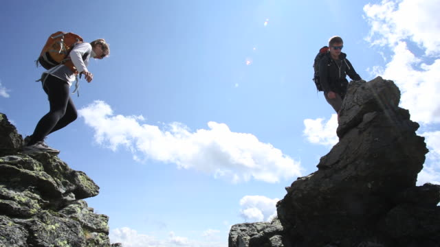 'Hikers jump between rocks on ridge crest, reach summit'