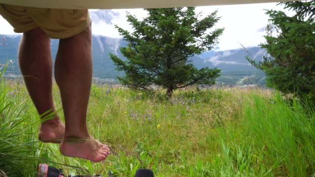 hiker's legs dangle above meadow after hike - legs crossed at ankle stock videos and b-roll footage
