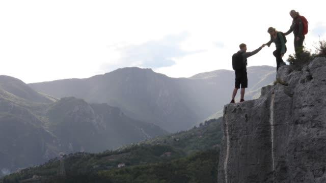 vidéos et rushes de hikers lend a helping hand while approaching cliff edge - se tenir par la main