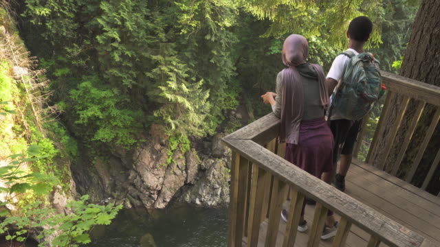 vidéos et rushes de hikers looking at waterfall from scenic viewpoint on summer evening - vêtement religieux