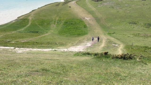 hikers on the seven sisters chalk cliffs - イーストサセックス点の映像素材/bロール