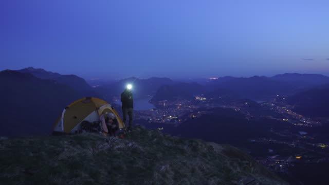 vidéos et rushes de randonneurs au sommet d'une montagne au crépuscule avec la ville de lac derrière - lampe frontale