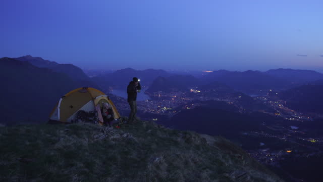 hikers on top of a mountain at dusk with lake town behind - head torch stock videos & royalty-free footage