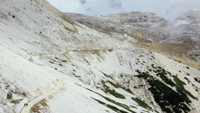 ha hikers on trail descending snow-covered mountain peak / italy - tre cimo di lavaredo stock videos & royalty-free footage