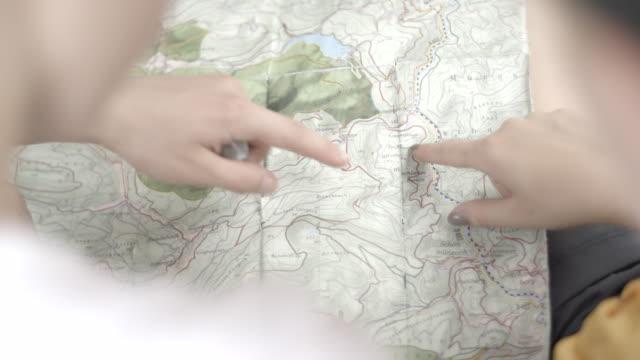vídeos de stock, filmes e b-roll de mapa de papel de referência de caminhantes - papel