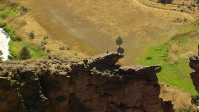 MS AERIAL Hikers resting atop rock formation with Monkey Face and Smith Rock / Terrebonne, Oregon, United States