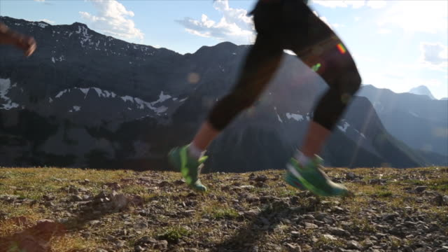 vídeos y material grabado en eventos de stock de hikers run along high ridge crest, above mountains - parte inferior
