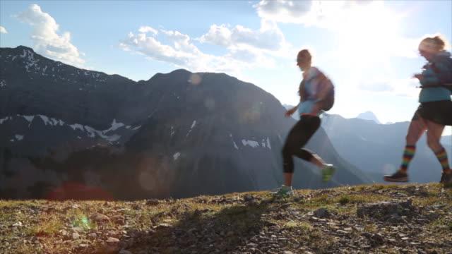Hikers run along high ridge crest, above mountains