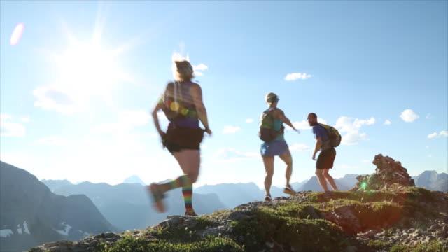 Hikers run along high ridge crest, take smart phone pic