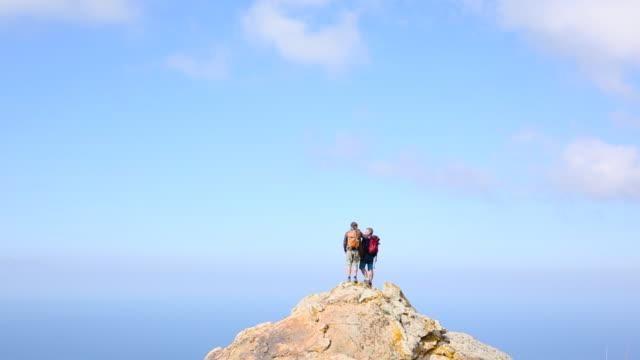 Hikers scramble to summit of peak, look out across sea