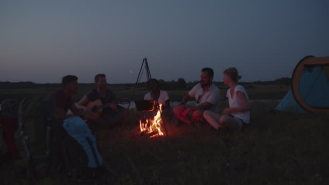 4K: Hikers Singing And Playing Guitar Around Campfire.
