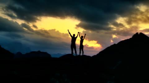 vídeos de stock, filmes e b-roll de hd: caminhantes em um pico de pé com as mãos levantadas - realização