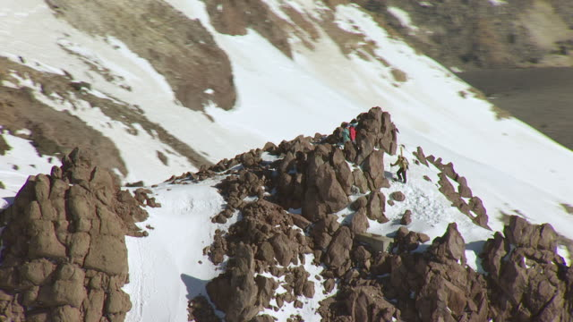 WS ZO AERIAL POV Hikers standing on snowy mountain at Lassen Volcanic National Park, California