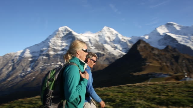 hikers traverse high alpine meadow at sunrise - switzerland stock videos & royalty-free footage