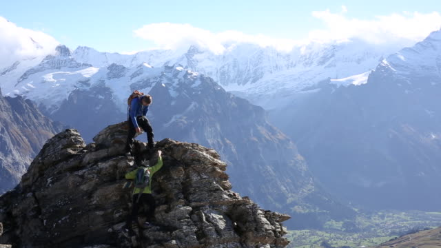 hikers traverse rocky alpine ridge, at summit - moving up stock videos & royalty-free footage