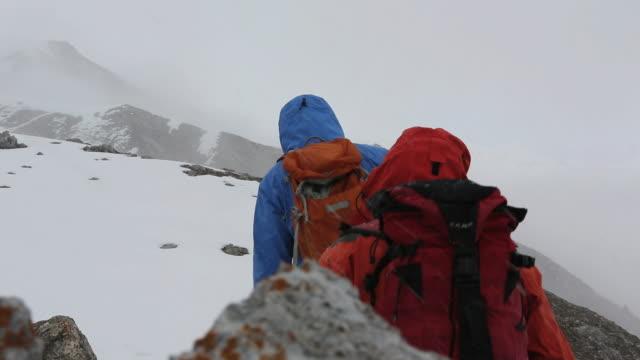 hikers traverse snowy terrain in heavy snowstorm - cappotto invernale video stock e b–roll