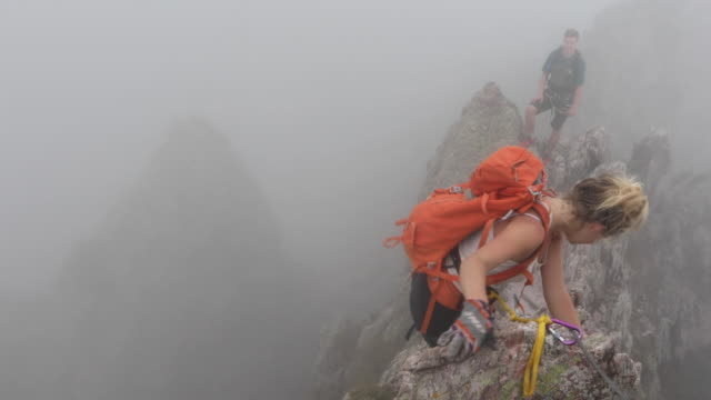 hikers traverse via ferrata route into mist - metal clip stock videos and b-roll footage