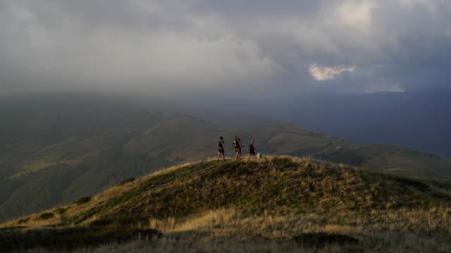 vidéos et rushes de randonneurs randonnée sur la crête montagneuse au coucher du soleil - scène tranquille