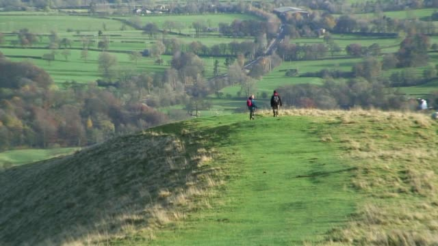 Hikers walk along a lush green hillside overlooking Derbyshire, England.