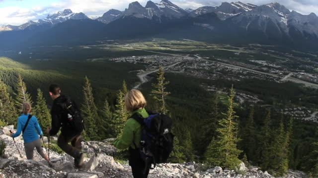 hikers walk along trail above mountain valley - gemeinsam gehen stock-videos und b-roll-filmmaterial
