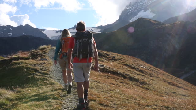 hikers walk along trail below matterhorn, sunrise. - maglietta video stock e b–roll
