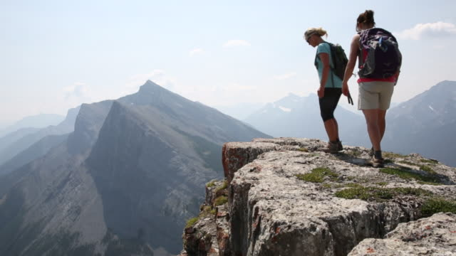 Hikers walk to edge of rock cliff, look down and across valley