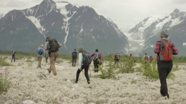 hikers walking across a glacier plain in the mountains - jamaican ethnicity stock videos & royalty-free footage
