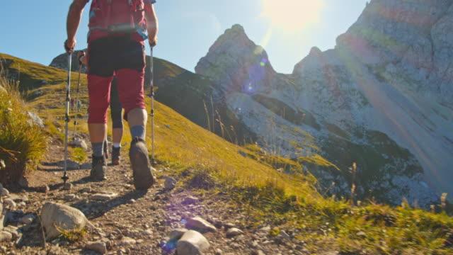 stockvideo's en b-roll-footage met ws wandelliefhebbers wandelen op een bergpad - julian alps