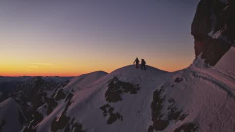 vídeos y material grabado en eventos de stock de los excursionistas caminan en la cresta cubierta de nieve al amanecer - deporte de riesgo