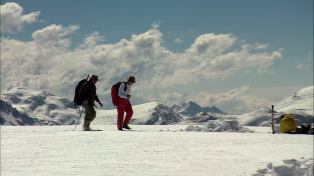 TS Hikers walking through snow towards a scientific base camp with instruments in the snow