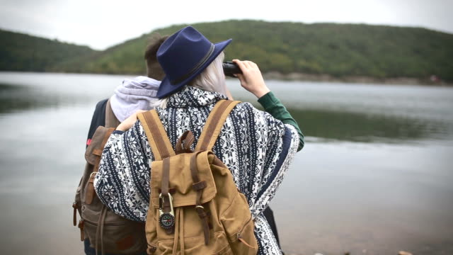 hikers watching the view on the lake - binoculars stock videos & royalty-free footage