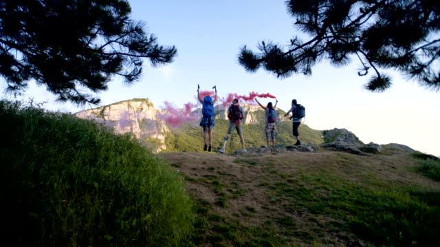 Hikers with red smoke on top of the mountain