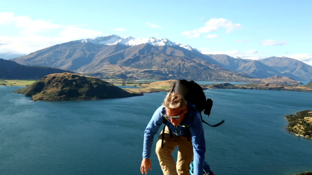 hiking couple ascend final ridge and look out at mountain lake view - otago region stock videos & royalty-free footage