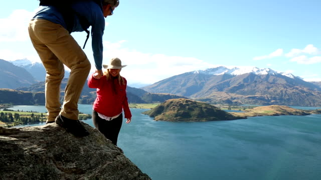 hiking couple ascend final ridge and look out at mountain lake view - heterosexuelles paar stock-videos und b-roll-filmmaterial