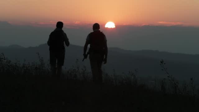 ハイキングカップルは、勇敢な、日の出の上の丘の中腹に登ります - 谷点の映像素材/bロール