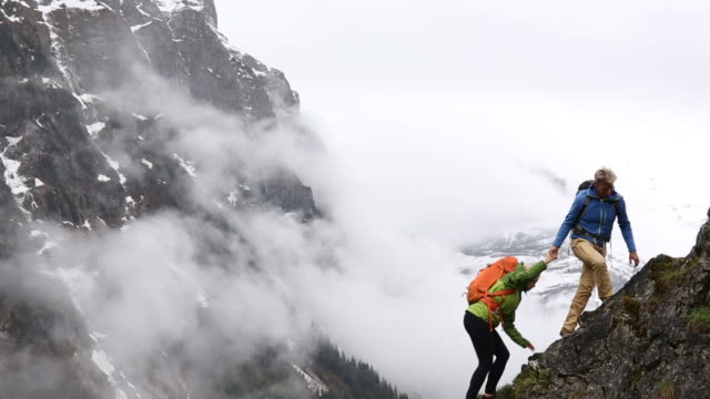 hiking couple ascend ridge, man provides assistance to woman - wandern stock-videos und b-roll-filmmaterial