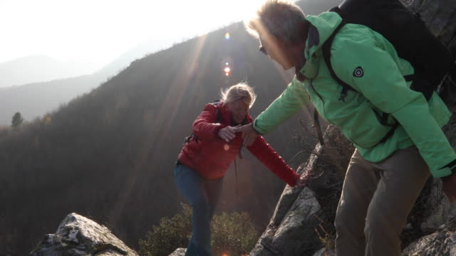 hiking couple ascend rock ridge, above mountains - adventure stock videos & royalty-free footage