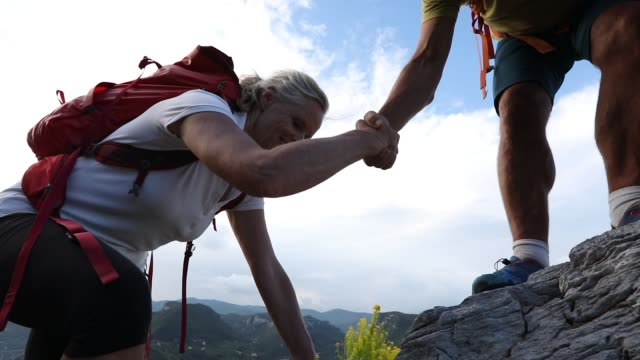 hiking couple ascend rock ridge above valley, village - top video stock e b–roll