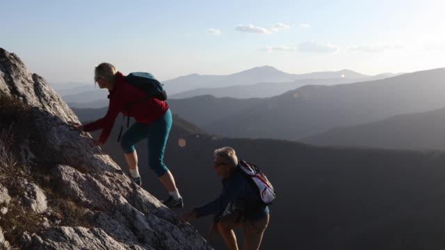 Hiking couple ascend rock ridge to summit