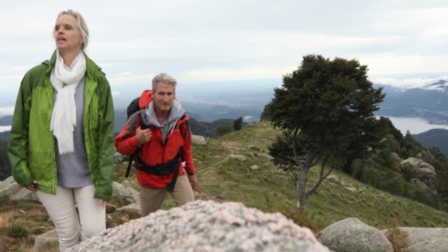 hiking couple ascend through alpine rocks under rainy sky - mature couple stock videos & royalty-free footage