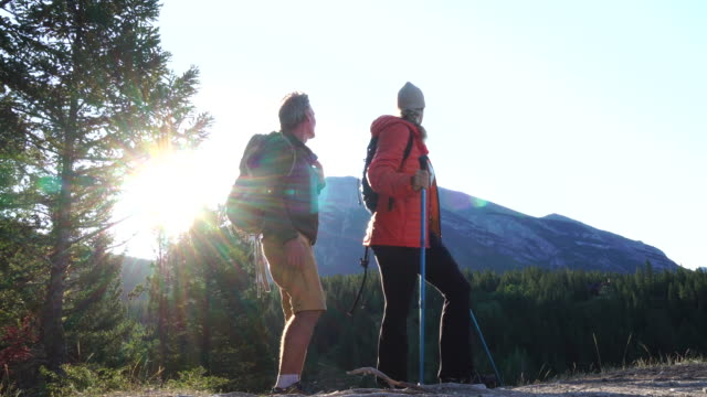 hiking couple ascend trail, look out across mountains and forest - orange colour stock videos & royalty-free footage