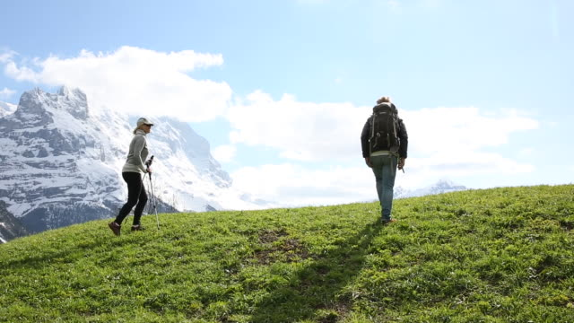 Hiking couple ascends green meadow below snow capped mountains