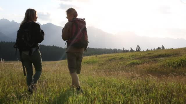 vídeos de stock, filmes e b-roll de hiking couple cross mountain meadow, take smart phone pic - smart