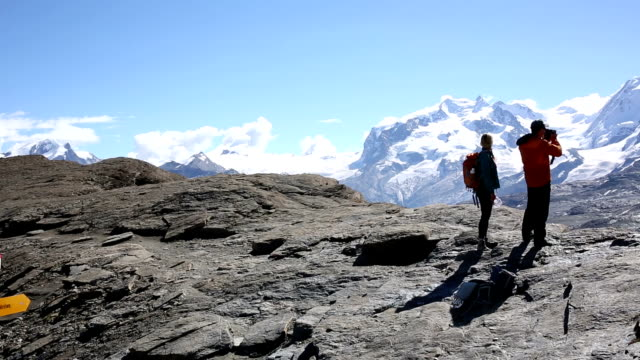 hiking couple descend slope below matterhorn - directional sign stock videos & royalty-free footage