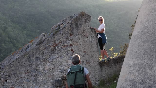 Hiking couple explore ancient castle remains, mountains