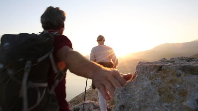 hiking couple explore rock bluff above coastline, sea - liguria stock videos & royalty-free footage
