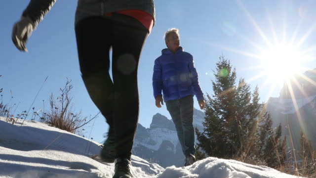 hiking couple follow mountain track through snow, at sunrise - outdoor pursuit stock videos & royalty-free footage