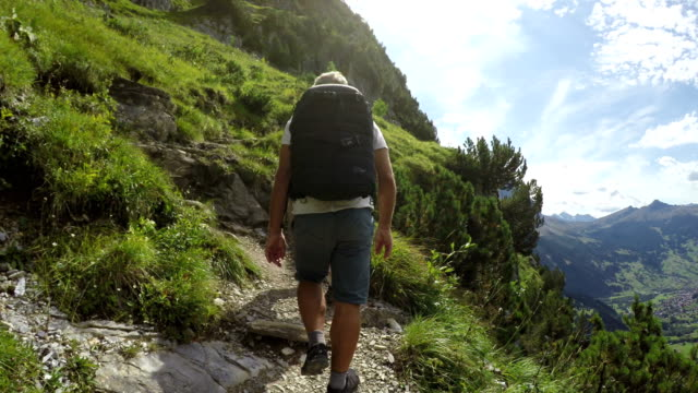 hiking couple follow trail along open slope, in mountains - schweiz stock-videos und b-roll-filmmaterial