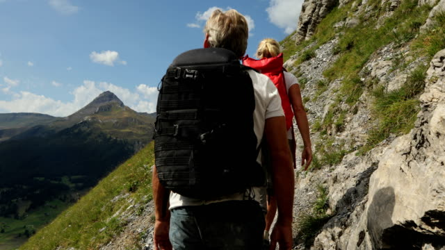 Hiking couple follow trail along open slope, in mountains
